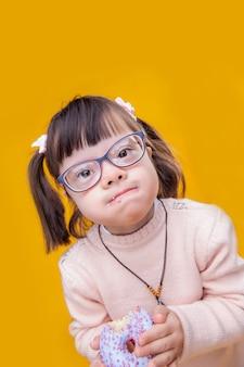 Brokkelt overal af. geïnteresseerd klein kind met een duidelijke bril en een mond vol smakelijke donut