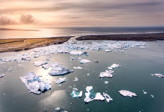 Brokken ijs verspreid over een gletsjerlagune in ijsland met bergen bedekt met sneeuw
