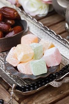Brokken lokum of turks fruit in een traditionele koperen vaas op metalen dienblad