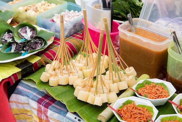 Brokken ruw suikerriet op stokken te koop in walking street in thailand.