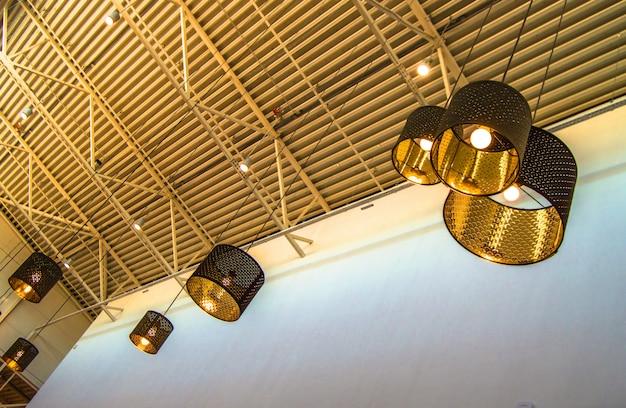 Bronskleurige decoratieve lampen in moderne stijl en gouden lampenkappen hangen aan een lang touw