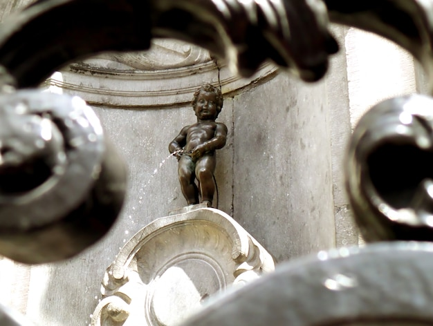 Bronzen beeld van manneken pis als view through iron fence