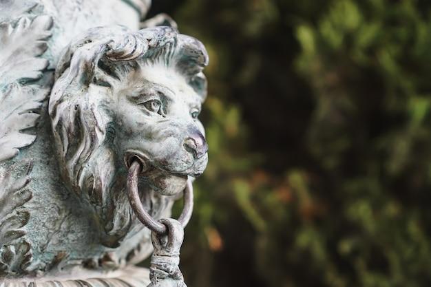 Bronzen leeuwenkop van metaal op een zuil in het park.