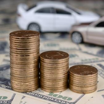 Bronzen munten stapels met wazig speelgoed auto's op de achtergrond
