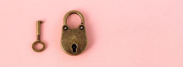 Bronzen sleutel en hangslot op zacht roze papier,