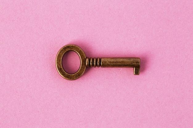 Bronzen sleutel op zacht roze papier, achtergrondafbeelding