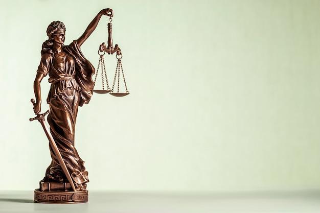 Bronzen standbeeld van justitie met zwaard en schalen