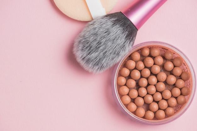Bronzende parels met make-upborstel op roze achtergrond