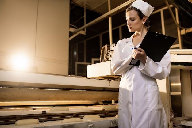 Brood. brood productielijn. vrouw in uniform. sanitaire controle.