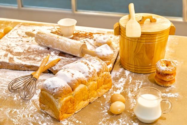 Brood, eieren, melk, donuts en verse melk op houten tafel in de buurt van venster. ontbijt bereiding