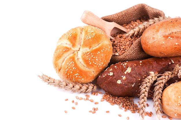 Brood en broodjes op servet dat op witte ruimte wordt geïsoleerd. diverse soorten brood geïsoleerd op een witte ruimte