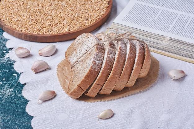 Brood gemaakt van bloem voor alle doeleinden op blauwe tafel.