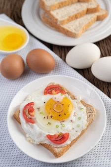 Brood geplaatst met een gebakken ei met tomaten, tapiocameel en gesneden lente-uitjes.