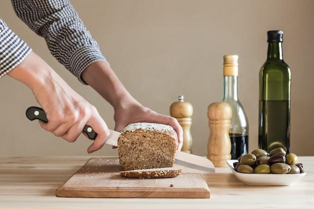 Brood gesneden door vrouwelijke handen in de keuken