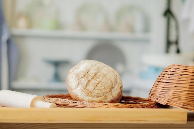 Brood in de buurt van een rieten mand op een tafel in een rustieke keuken.