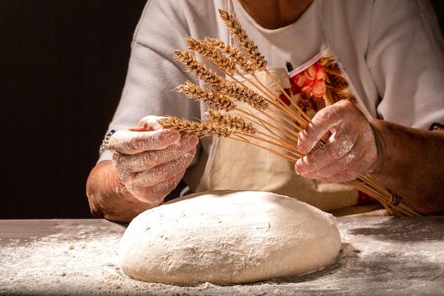 Brood in de oude gerimpelde handen van de grootmoeder close-up. oma's brooddeeg. grootmoeder die een stuk brood met tarweoren houdt. oude vrouw met brood