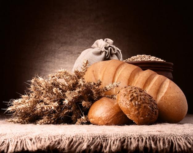 Brood, meelzak en orenbosstilleven op rustiek