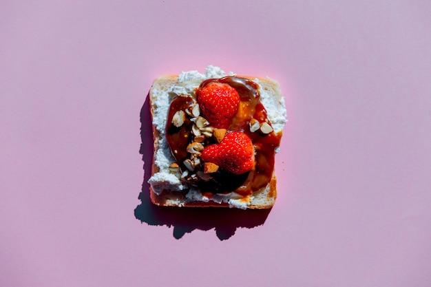 Brood met aardbei, kaas en chocoladeroom op paarse achtergrond