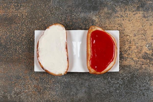 Brood met aardbeienjam en zure room op witte plaat.