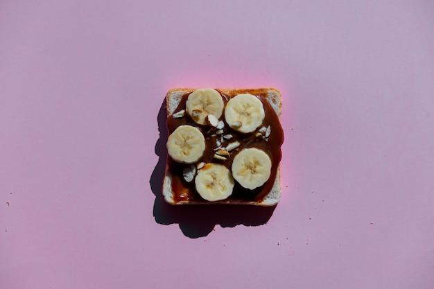 Brood met banaan, kaas en chocoladeroom op paarse backgrpund