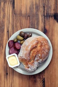 Brood met boter, olijven en rookworst op schotel op houten oppervlak