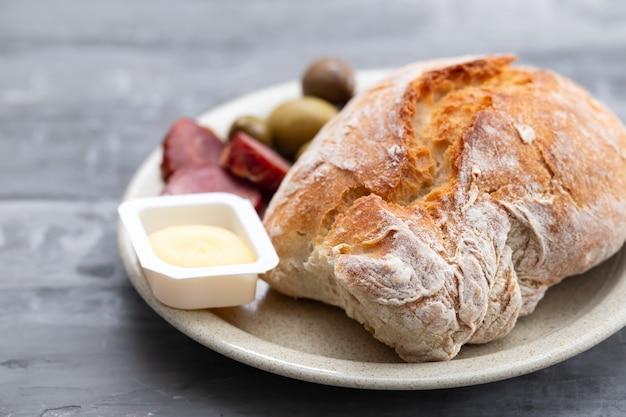 Brood met boter, olijven en rookworst op schotel op keramisch oppervlak