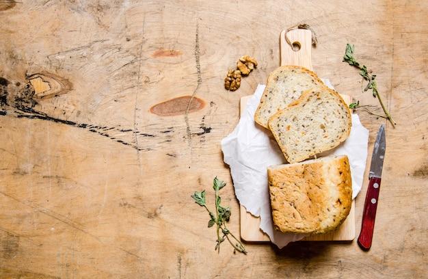 Brood met kruiden en mes aan boord. op een houten tafel.