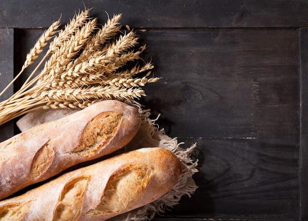 Brood met tarwe oren op houten tafel, bovenaanzicht