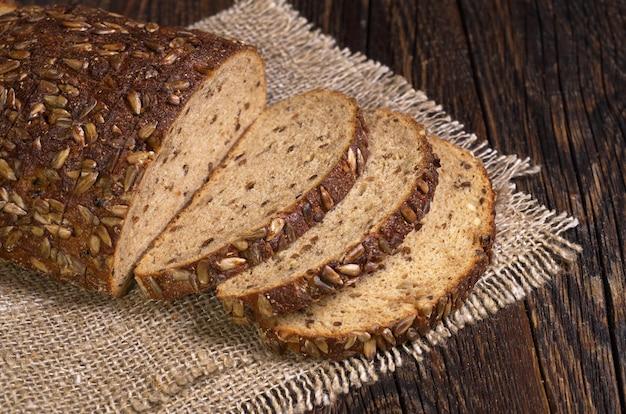 Brood met zaden en plakjes gedroogd fruit op oude houten tafel