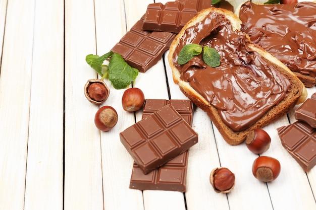 Brood met zoete chocolade hazelnootpasta op houten tafel