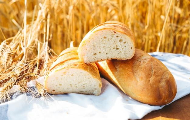 Brood op de tafel en tarwe op het gebied van tarwe en zonnige dag
