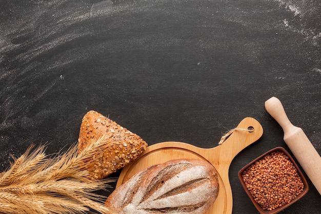 Brood op een houten bord en deegrol met tarwe