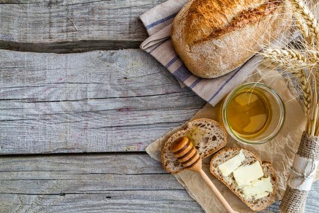 Brood, rogge, tarwe, honing, melk rustieke houten achtergrond
