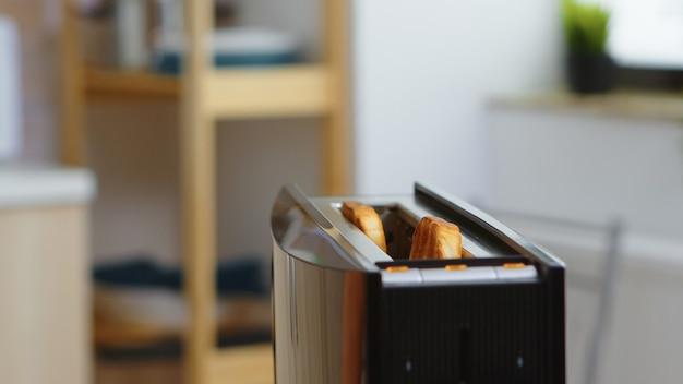 Brood roosteren dat uit de broodrooster in de keuken springt voor het ontbijt. broodbereiding voor heerlijk ontbijt. gezonde ochtend in gezellig interieur, heerlijke thuismaaltijdbereiding