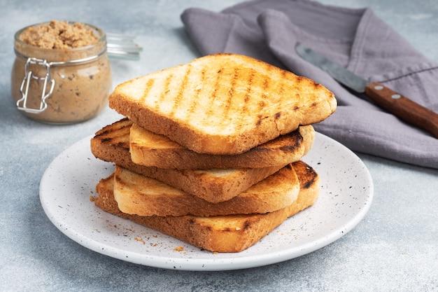 Brood toast knapperig voor broodjes op een bord op een grijze betonnen tafel. een potje kippenpastei.