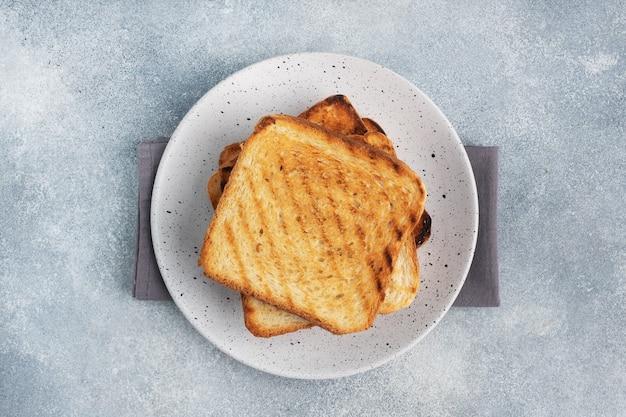Brood toast knapperig voor broodjes op een bord op een grijze betonnen tafel. ruimte kopiëren.