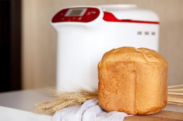 Brood uit een broodbakmachine met tarweaartjes op een bord met een keukenservet