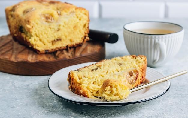 Brood van bananenbrood op een houten snijplank met kopje thee