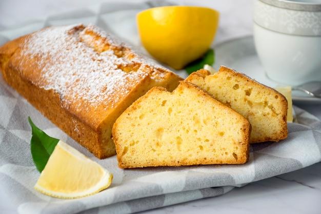 Brood van glutenvrije citroentaart, stukjes citroen en kopje op keukenpapier op marmeren tafel