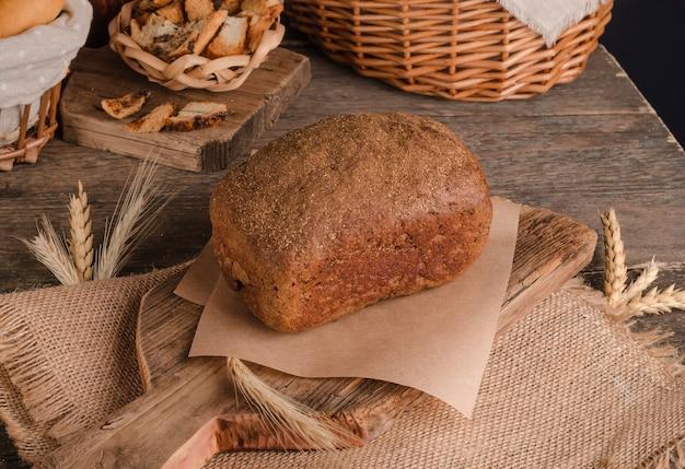 Brood van traditioneel roggebrood op houten achtergrond en jute