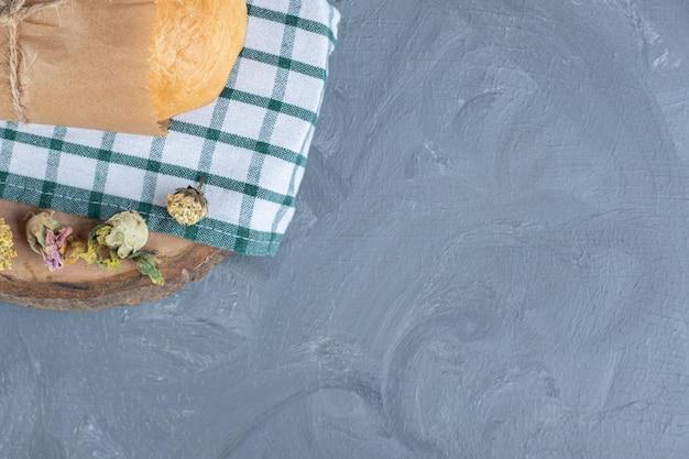Brood verpakt in papier op een gevouwen tafelkleed op marmeren achtergrond.