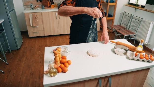 Broodbereiding thuis in de keuken door oude man. oudere senior bakker met bonete en uniform besprenkelen, zeven, met de hand nieuwe ingrediënten op deeg verspreiden, zelfgemaakte pizza en koekjes bakken