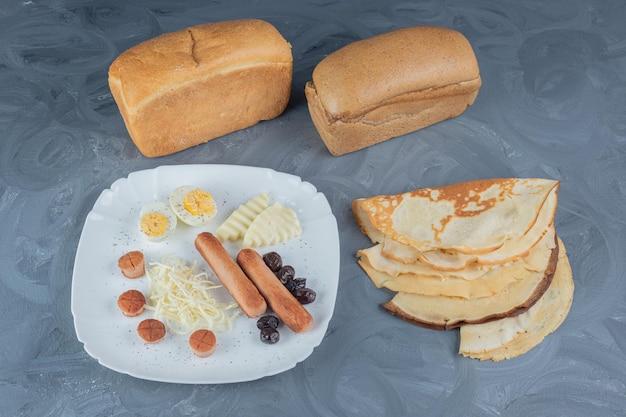 Broodblokken en pannenkoeken naast een ontbijtschotel op marmeren tafel.