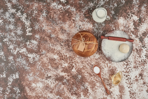 Broodbroodje op marmer met deeg en ingrediënten.