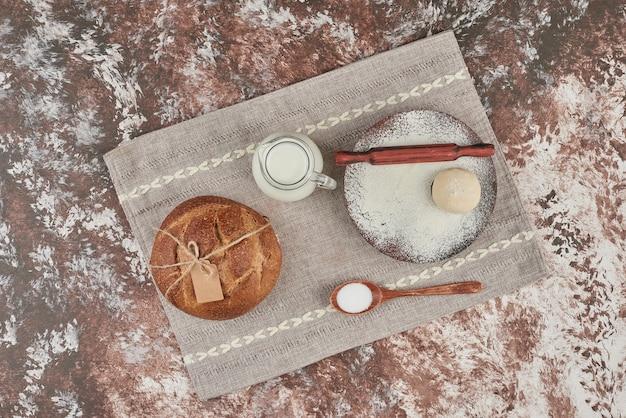 Broodbroodje op marmer met ingrediënten.