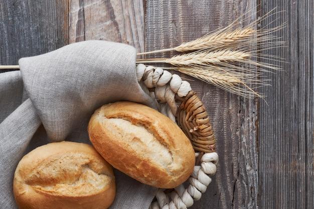 Broodbroodjes in mand op rustiek hout met tarweoren