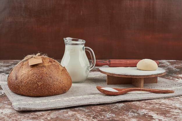 Broodbroodjes op grijze keukenhanddoek met ingrediënten.