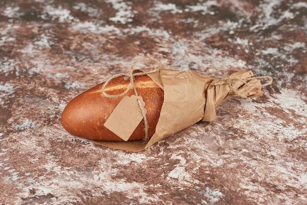 Broodbroodjes op het marmer in een papieren wikkel.