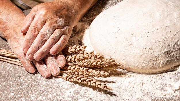 Brooddeeg klaar om te kneden. het deeg voorbereiden. vrouw overgrootmoeder kneeddeeg in zelfgemaakte keuken