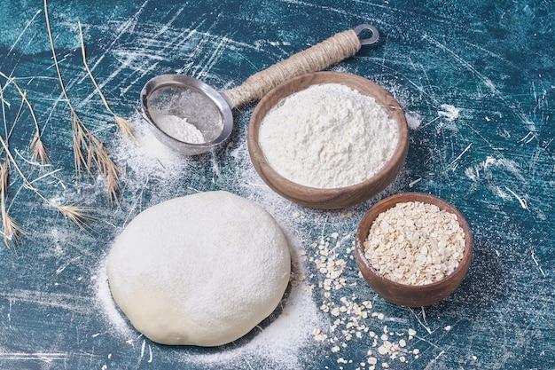 Brooddeeg met ingrediënten op blauwe tafel.